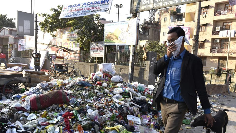 A man walks past a pile of garbage on a road at Vinod Nagar West in east Delhi on Tuesday. Garbage across east Delhi has not been picked up after sanitation workers went on a strike.