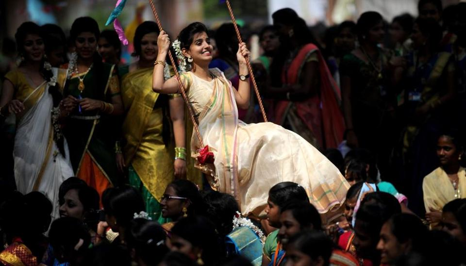 A student plays on a swing during celebrations of the Tamil harvest festival Pongal at a college in Chennai on Wednesday.  (AFP photo)