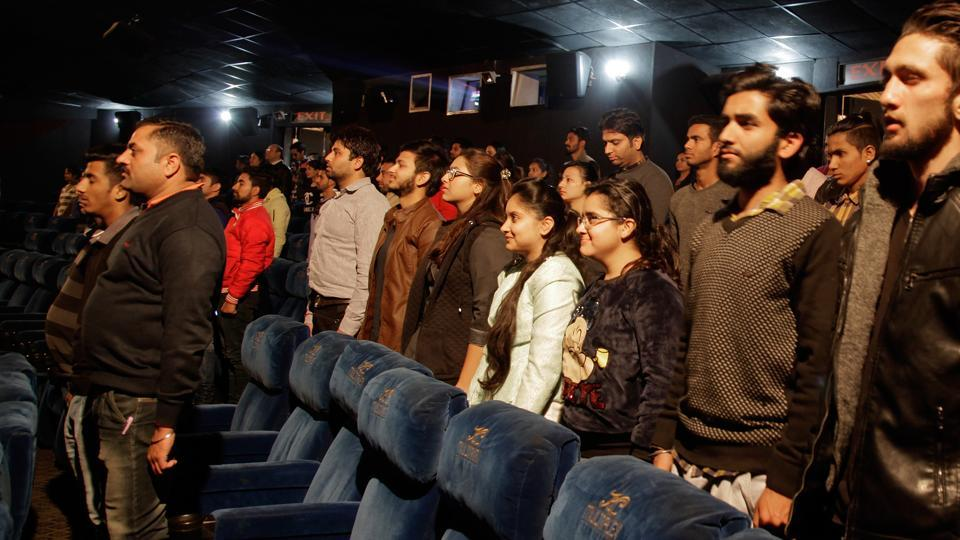 Indian movie goers stand up as national anthem is played at a movie hall before the screening of a movie in Jammu.