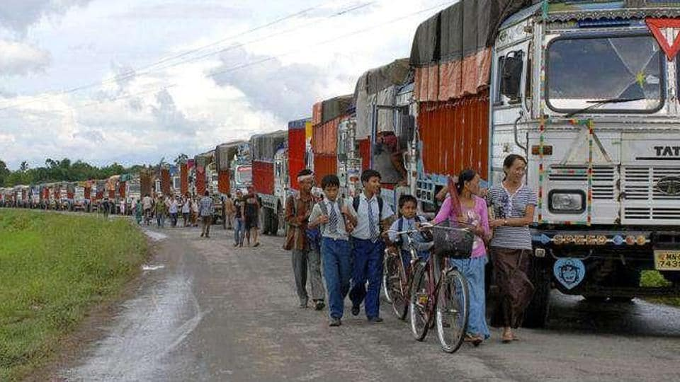 Schoolchildren and others walk past empty trucks parked in a row, waiting to be escorted by police to Assam to ferry supplies to Manipur, on the outskirts of Imphal.