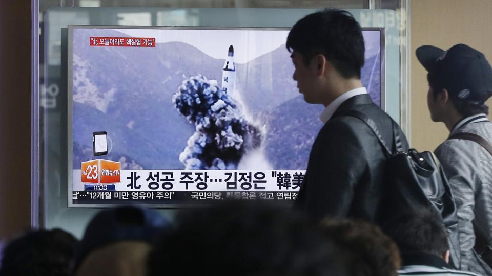 A man walks by as people watch a TV news program showing an image North Korea's ballistic missile that the North claimed to have launched from underwater, at Seoul Railway station in South Korea.