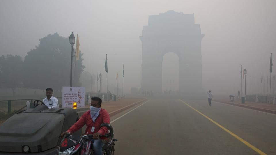 In this Monday, Oct. 31, 2016 photo, a man covers his face with a scarf as he rides in front of the landmark India Gate, enveloped by smoke and smog, on the morning following Diwali festival in New Delhi, India.