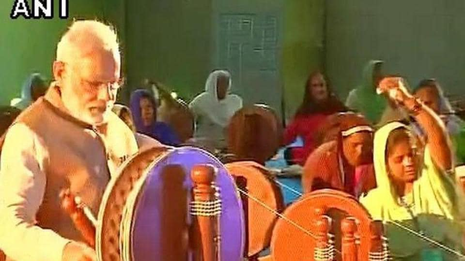 Narendra Modi trying his hand on the spinning wheel in an event in October 2016. The cover of the 2017 wall calendar and table diary published by the Khadi Village Industries Commission shows the PM weaving khadi on a large 'charkha', in the same classic pose as Gandhiji.