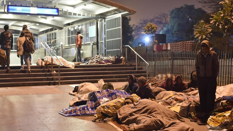 Patients at AIIMS and their families sleep outside the Metro Station in the open during extreme cold. (Saumya Khandelwal/HT PHOTO)