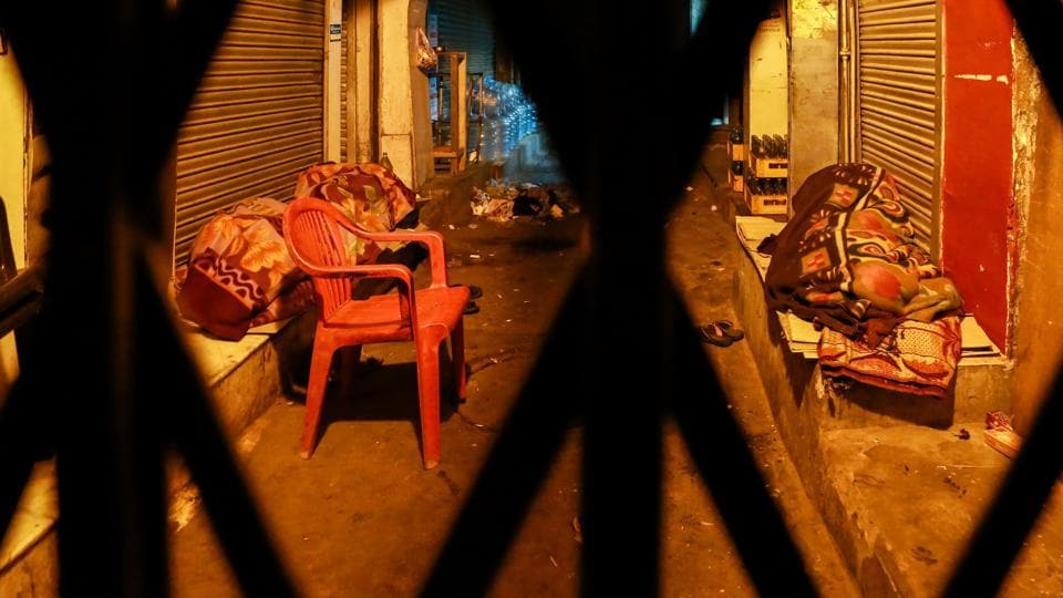 BEHIND BARS: Two daily wage workers sleep in front of shops in a lane at Chandni Chowk. (AMAL KS/HT PHOTO)