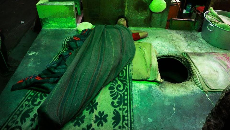 AT PEACE: A young worker sleeps next to a tandoor outside a shop near Jama Masjid. (AMAL KS/HT PHOTO)