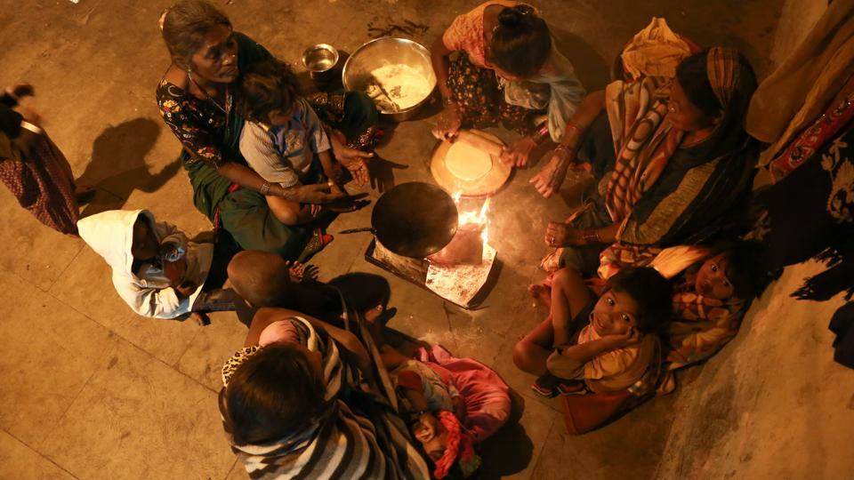 FOR THE SAKE OF LOVE: A group of women and children at Motia Khan huddles around a fire to keep warm while a woman cooks rotis for dinner.  (AMAL KS/HT PHOTO)