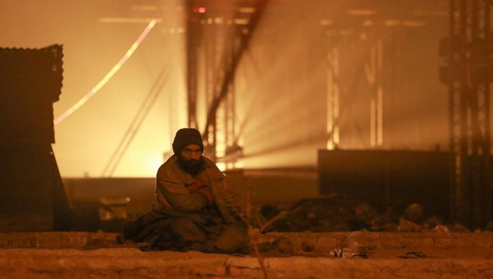 Wishing for the sun: A lone man sits at a metro construction site in Vasant Vihar. (AMAL KS/HT Photo)