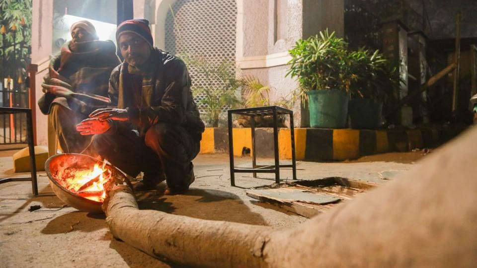 LIFE ON FIRE: While they keep watch outside a society at Mall Road, security guards warm themselves up with small bonfire. (AMAL KS/HT PHOTO)