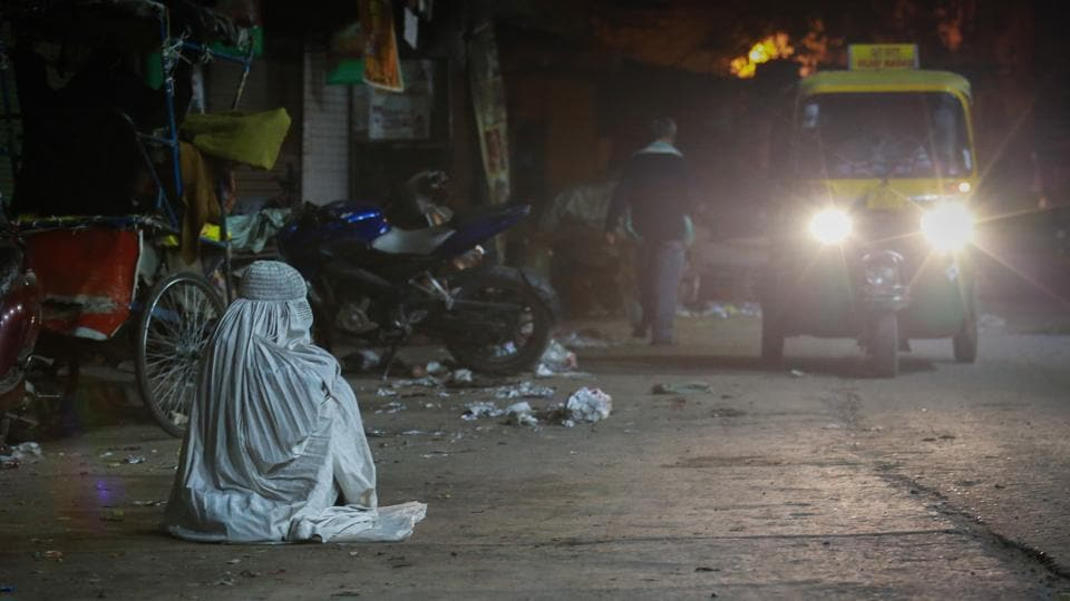 WAITING IN WHITE: A person wearing an Afghani burkha sits alone on the road at 4am near Turkman Gate. (AMAL KS/HT PHOTO)