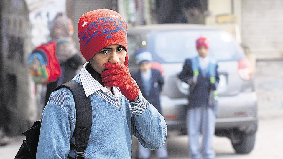 Schoolchildren wait for their bus at a stop in Noida on cold Thursday, a day the city recorded a minimum temperature of 3 degrees Celsius, the lowest so far this winter.