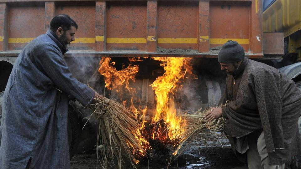 Drivers heating frozen truck fuel tank by burning fire below it on a cold winter morning in Srinagar. (waseem andrabi/ht photo)