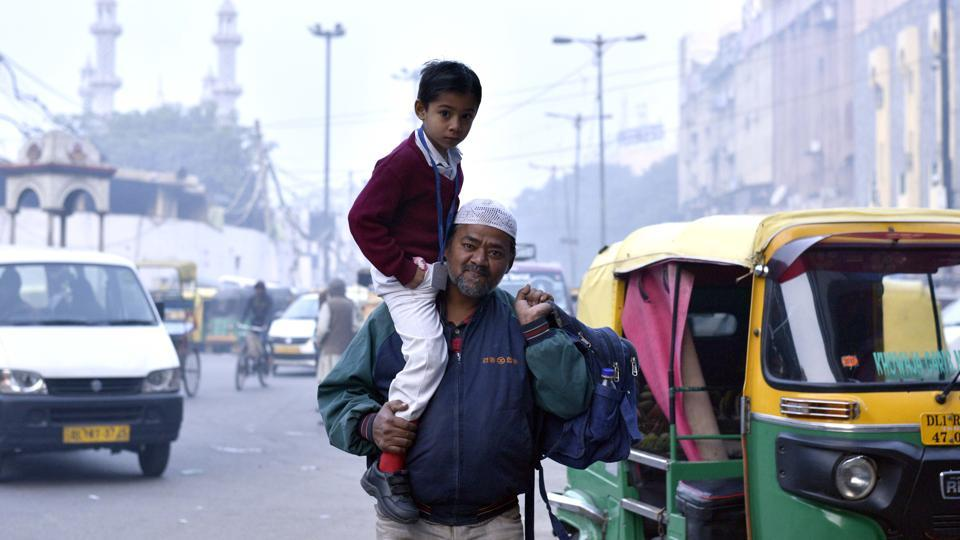 A man carries  his son to school on his shoulders on a cold winter morning in Old Delhi. (Arun Sharma/HT PHOTO)