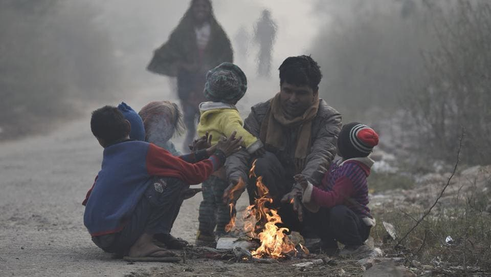 Homeless people warm themselves around a bonfire on a cold winter morning. Delhi today witnessed the coldest day of the season with temperature falling to 2.3 degrees Celsius at some parts of the national capital region in New Delhi. (Raj K Raj/HT PHOTO)