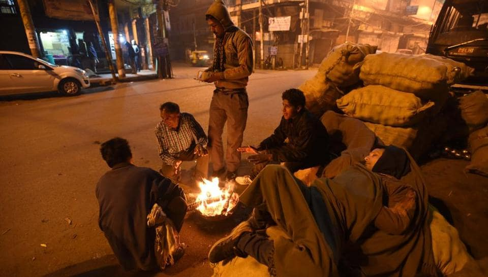 Homeless men sitting near the fire to stay warm on a cold winter morning in New Delhi.  (Arun Sharma/HT PHOTO)