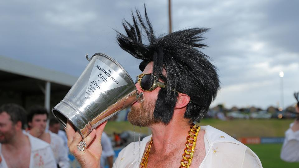 An amateur rugby player dressed as Elvis Presley drinks from the Memphis Mug trophy after the match between the Blue Suede Shoes and the Reddy Teddies at the 25th annual Parkes Elvis Festival. (REUTERS)