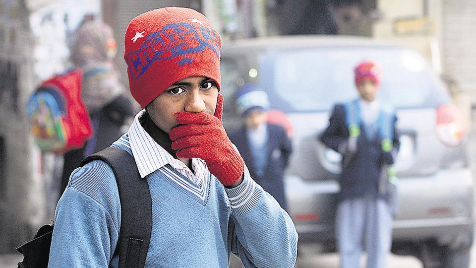 A school student waits for his bus on a cold morning, in Noida on Thursday