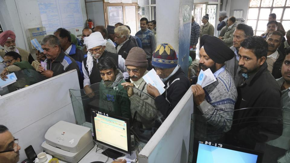 People stand in a queue to deposit notes in a bank in Samba district of Jammu and Kashmir.