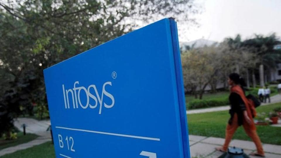 An employee walks past a signage board in the Infosys campus at the electronics city IT district in Bengaluru.