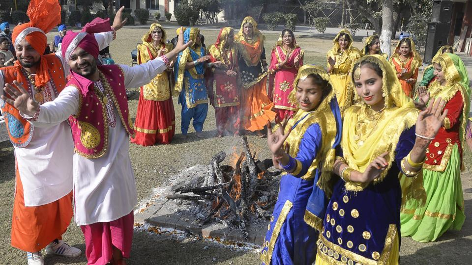 Students wearing traditional Punjabi attire dance around a bonfire during the Lohri festival celebration at Shahzada Nand College Amritsar on Friday.  (Gurpreet Singh/HT Photo)