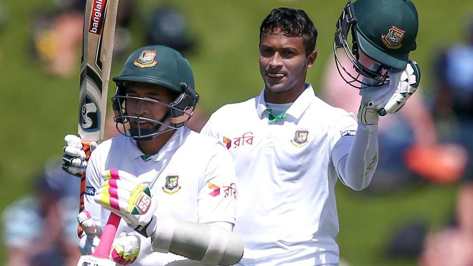 Shakib Al Hasan raises his bat after reaching his century enroute to a double while Mushfiqur Rahim, who too scored a big century looks on