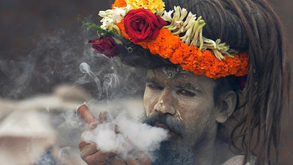 A naga sadhu smokes chillum on the way to Gangasagar mela (festival) at Babughat transit camp in Kolkata, India, on Wednesday, January 11, 2017.  (Samir Jana/HT  Photo)