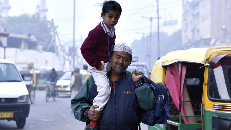 A man carries his son to school on a cold winter morning in old Delhi on Thursday, Jan 12, 2017.  The Kejriwal government has extended the winter break for primary classes from Jan 16-19 in view of the prevailing cold conditions.