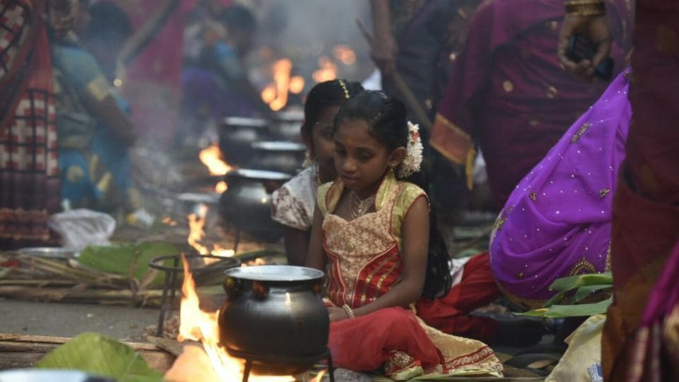 Tiny flames light up the road as devotees prepare rice dishes to offer to the Hindu Sun God in Dharavi, Mumbai.