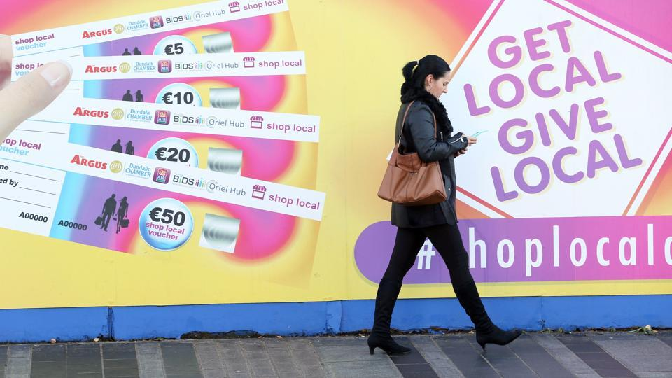 A woman walks past a poster advertising vouchers, a form of alternative currency aimed at boosting local shopping in the border town of Dundalk, Northern Ireland.
