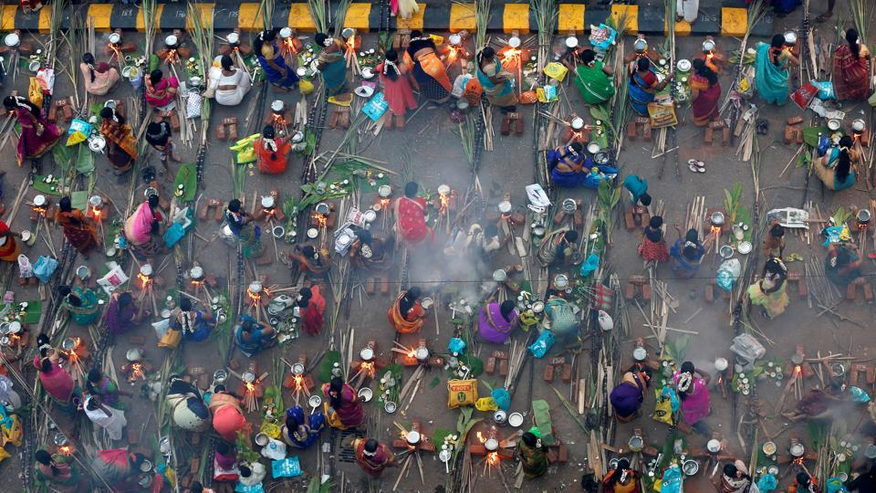 Devotees prepare rice dishes to offer to the Hindu Sun God as they attend Pongal celebrations early morning in Mumbai. (REUTERS)
