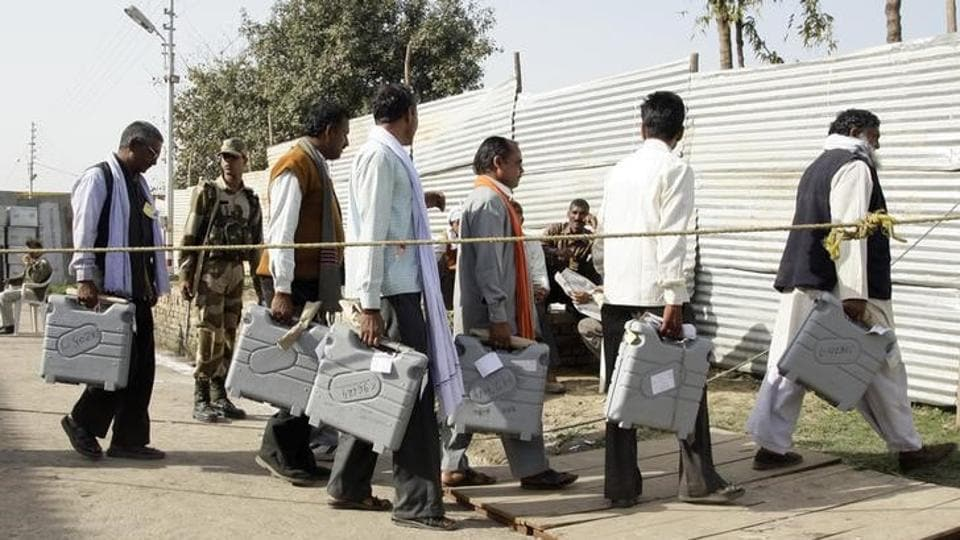 Election officials carry electronic voting machines (EVMs) as they arrive to count ballots at a counting centre in Allahabad.