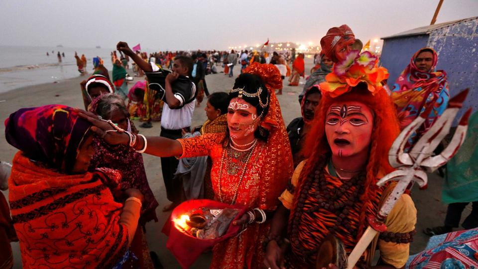 Two men dressed as Lord Shiva and Goddess Parvati give blessings to a pilgrim at the confluence of the river Ganges and the Bay of Bengal, ahead of the