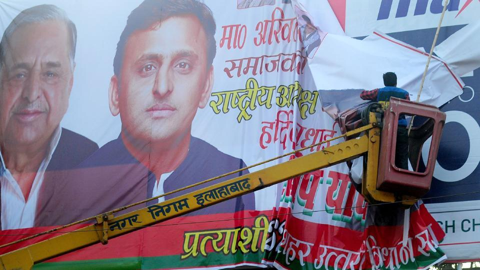 A municipal corporation  worker removes a banner poster of Uttar Pradesh chief minister, Akhilesh Yadav and his father Mulayam Singh Yadav. The manner in which the members of a high-profile family are fighting with each other gives rise to a question: Are their personal ambitions dearer to them than the electoral fortunes of their party?