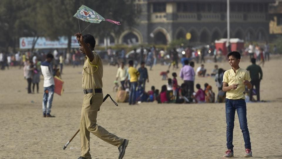 A child looks on as a police constable takes away his kite at Girgaum beach. (Arijit Sen/HT PHOTO)