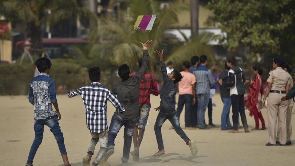 Youngsters run after kites at Girgaum beach. (Arijit Sen/HT PHOTO)