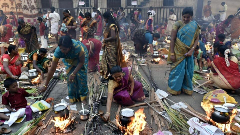Devotees prepare a traditional sweet dish on open fires during an event marking Pongal festival at Dharavi in Mumbai on Saturday, January 14, 2016.