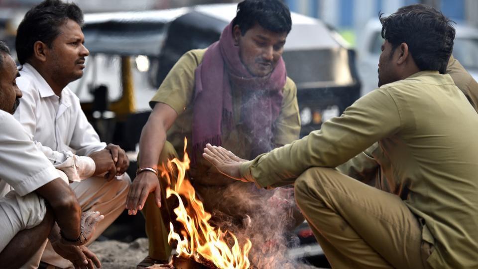 Auto rickshaw drivers start a bonfire to beat the cold at Ghatkopar on Friday.