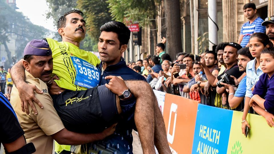 Pramod Nair, a  participant of half marathon was carried by a policemen and a volunteer during half marathon. (kunal patil/ht photo)