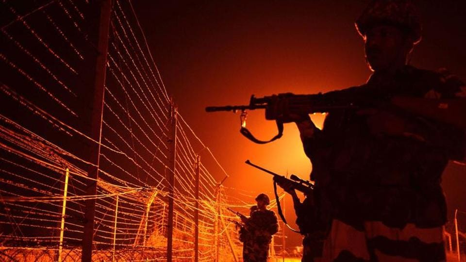 Border Security Force (BSF) soldiers patrol along a border fence at an outpost along the Line of Control (LOC) between India-Pakistan.