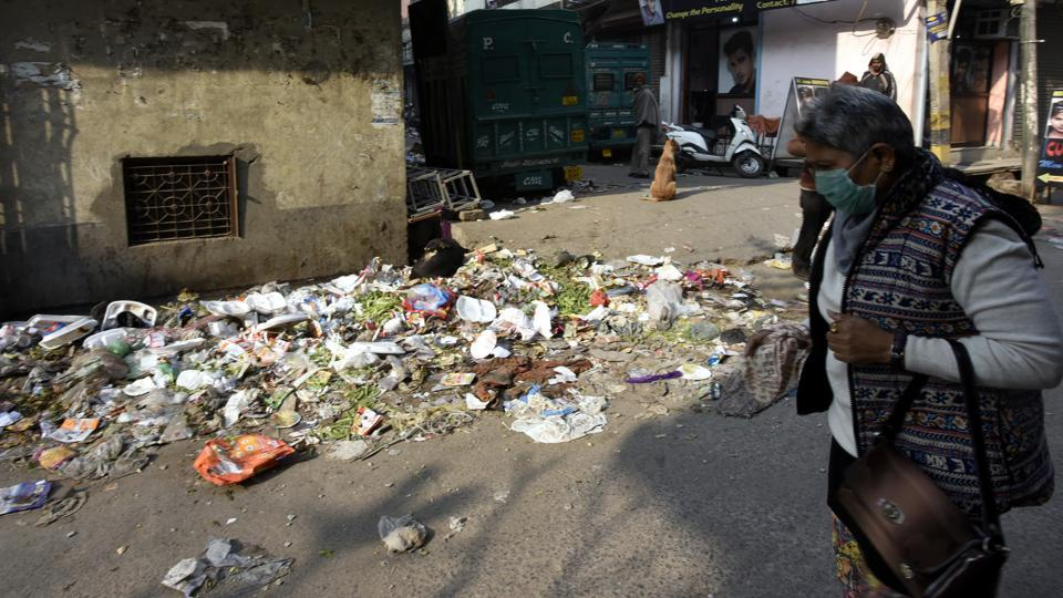 A woman covers her face as she walks past a garbage dump on Krishna Nagar road.