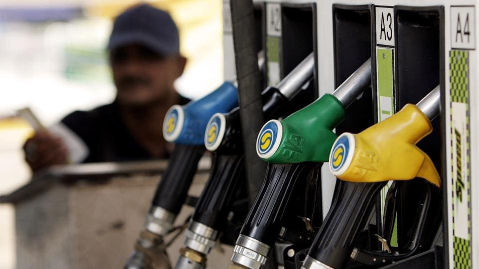 A petrol pump attendant waits for customers at a station in New Delhi.