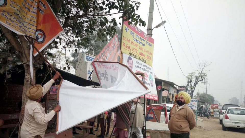 Officials removing hoardings by political parties in Ludhiana on Saturday.