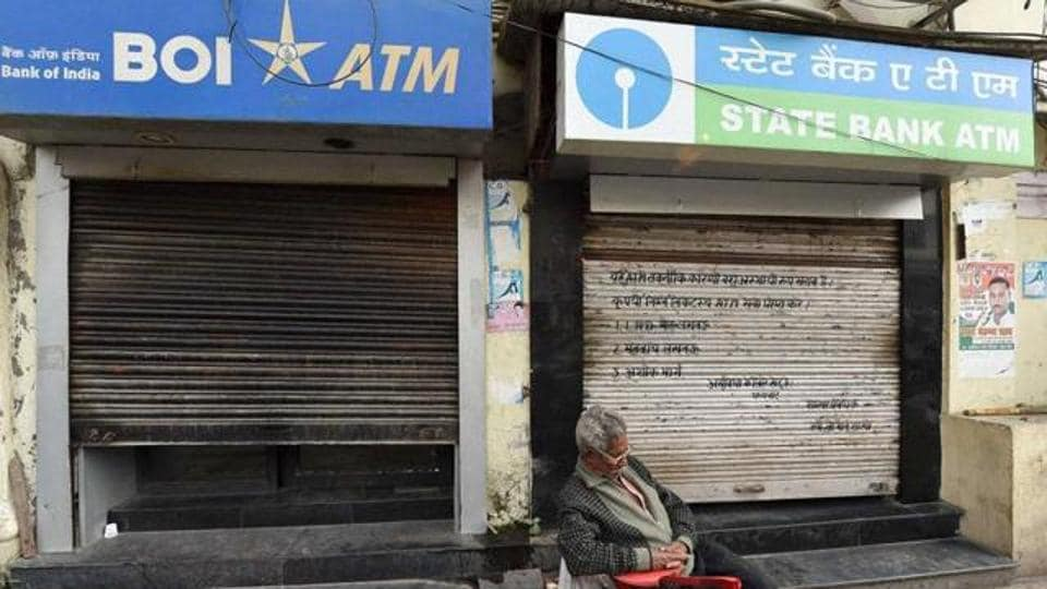 A man takes a nap outside the ATMwhich was closed due to unavailability of cash.