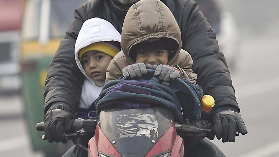 Two boys wearing jackets and holding a protective layer as their father rides them to school on a cold winter morning in New Delhi. (Raj K Raj/HT Photo)