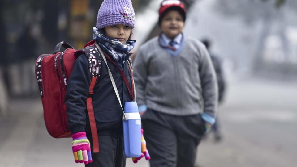 """Bring'em on!"" A girl fully prepared for the cold waits for her school bus at a pick-up location in New Delhi one winter morning. (Raj K Raj/HT PHOTO)"