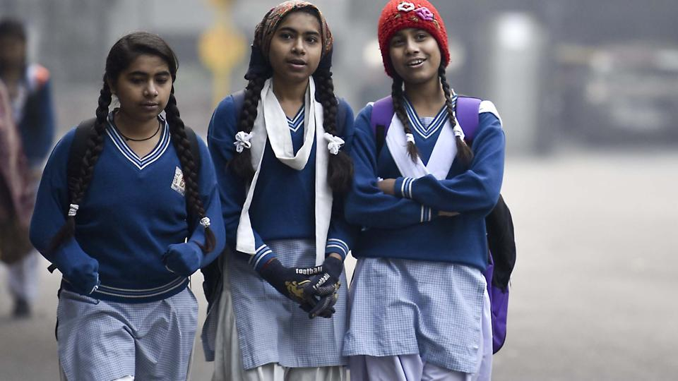Girls walk to school on a cold winter morning with overcast skies. (Raj K Raj/HT PHOTO)