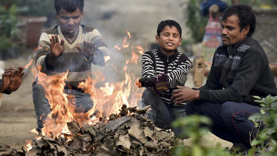 People gain warmth from burning leaves on a Delhi road during an intense cold morning. The city temperature has been dropping to around 6 degree Celsius. (Raj K Raj/HT PHOTO)