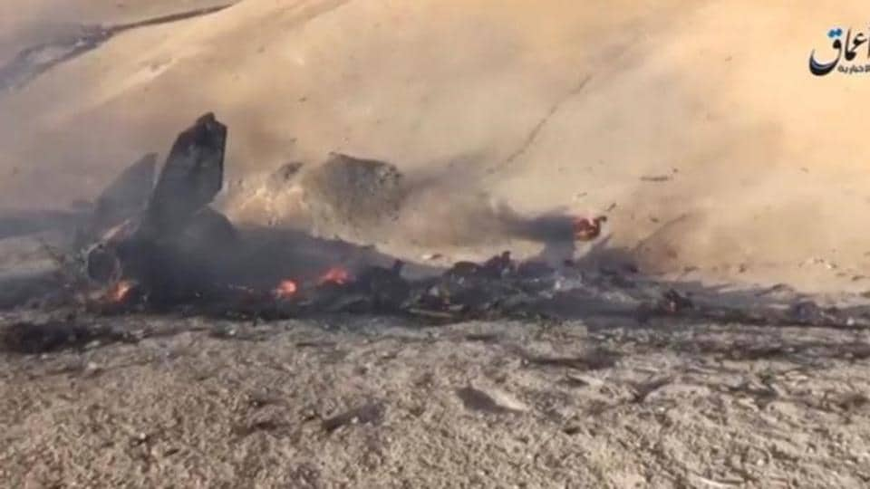 A still image taken on July 14, 2016 from a video posted on social media said to be shot today, July 14, 2016, shows the wreckage of a Syrian jet that was brought down by Islamic State fighters near the eastern city of Deir al-Zor, Syria.