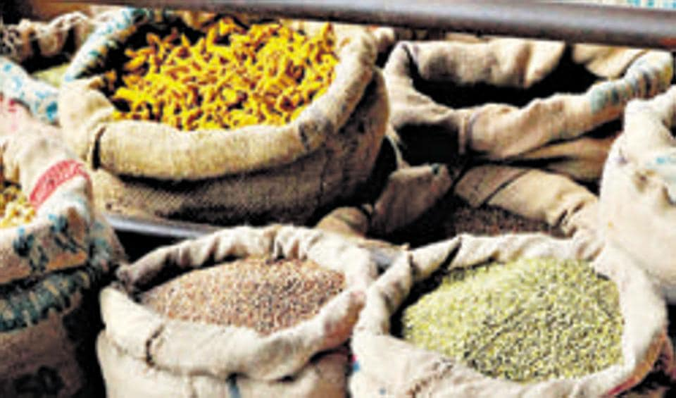 Workers and customers look through the goods at a wholesale food grain and commodities shop in the Agricultural Product Marketing Committee (APMC) Yard in Bangalore.