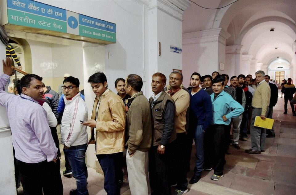 Employees of the finance ministry stand in a queue to withdraw cash from an ATM at North Block in New Delhi.